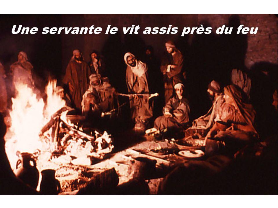 Une servante le vit assis près du feu