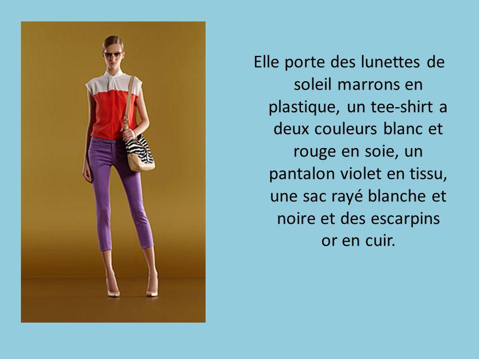 Elle porte des lunettes de soleil marrons en plastique, un tee-shirt a deux couleurs blanc et rouge en soie, un pantalon violet en tissu, une sac rayé