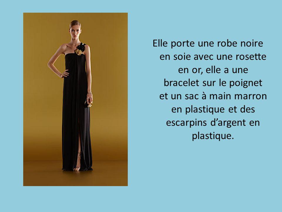 Elle porte une robe noire en soie avec une rosette en or, elle a une bracelet sur le poignet et un sac à main marron en plastique et des escarpins dar