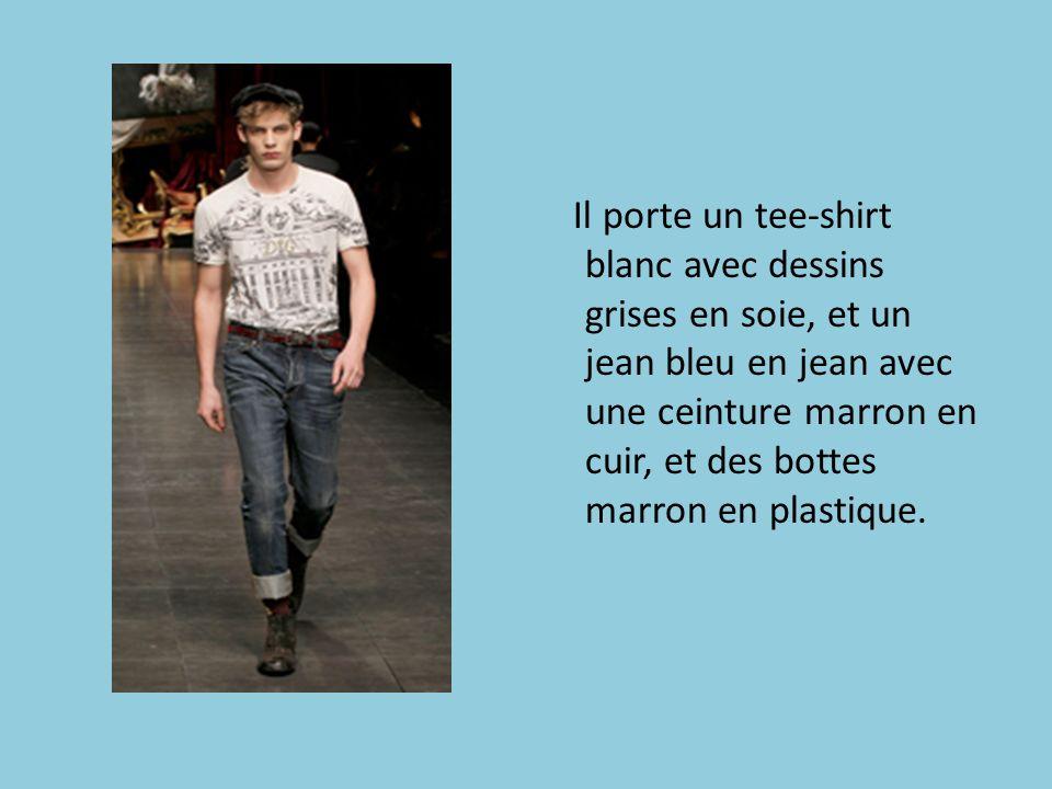 Il porte un tee-shirt blanc avec dessins grises en soie, et un jean bleu en jean avec une ceinture marron en cuir, et des bottes marron en plastique.