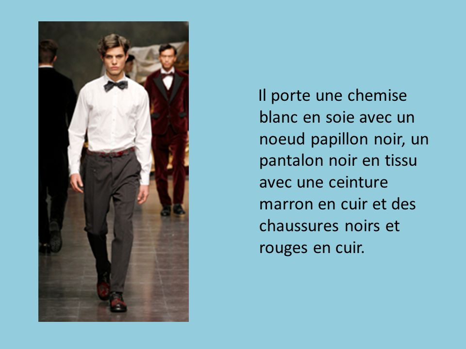 Il porte une chemise blanc en soie avec un noeud papillon noir, un pantalon noir en tissu avec une ceinture marron en cuir et des chaussures noirs et