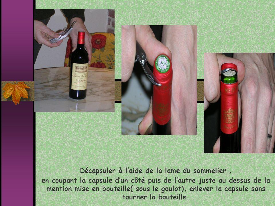 Décapsuler à laide de la lame du sommelier, en coupant la capsule dun côté puis de lautre juste au dessus de la mention mise en bouteille( sous le gou