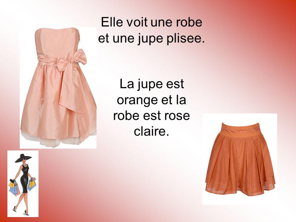 Elle voit une robe et une jupe plisee. La jupe est orange et la robe est rose claire.