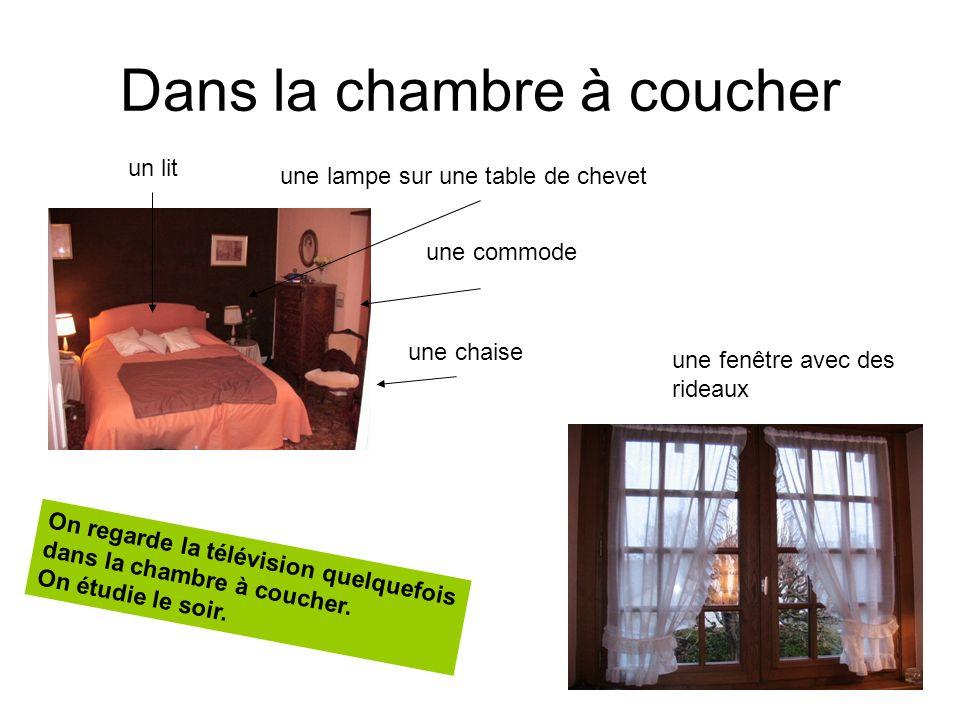Dans la chambre à coucher un lit une commode une chaise une lampe sur une table de chevet une fenêtre avec des rideaux On regarde la télévision quelqu