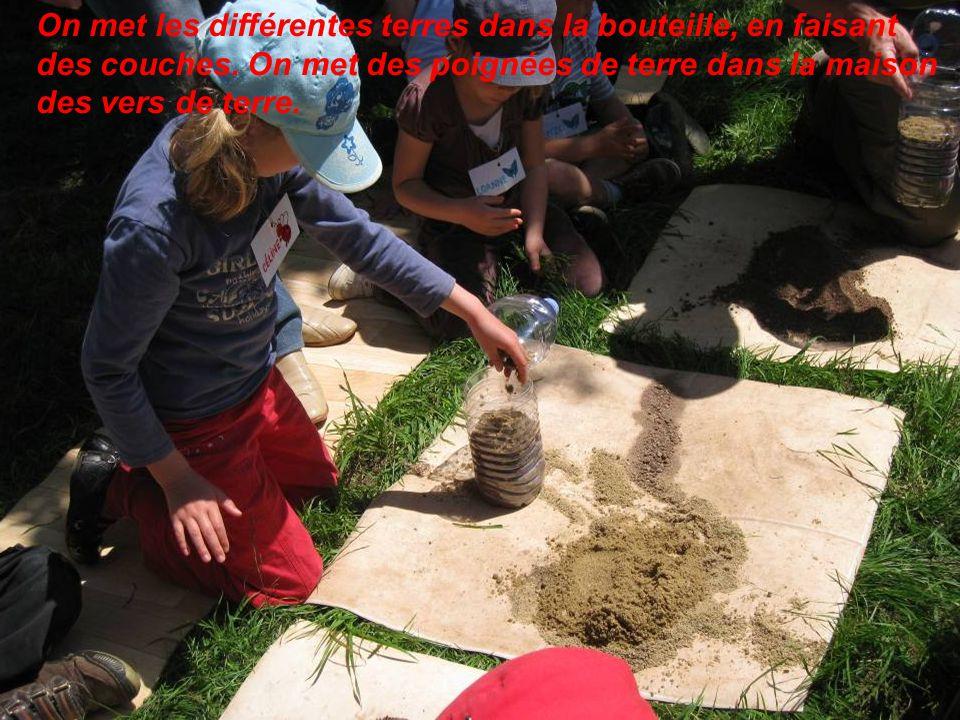 On met les différentes terres dans la bouteille, en faisant des couches. On met des poignées de terre dans la maison des vers de terre.