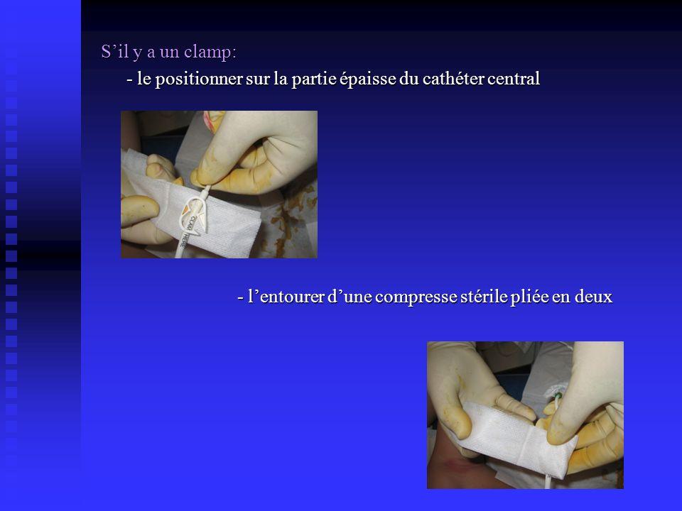 Sil y a un clamp: - le positionner sur la partie épaisse du cathéter central - lentourer dune compresse stérile pliée en deux