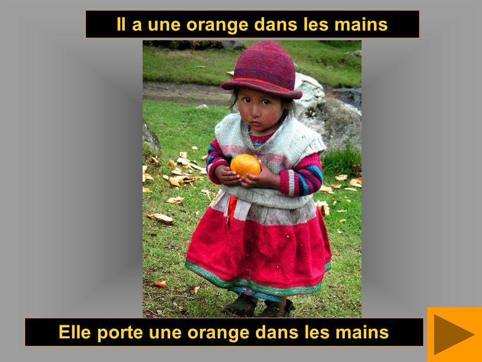 Il a une orange dans les mains Elle porte une orange dans les mains