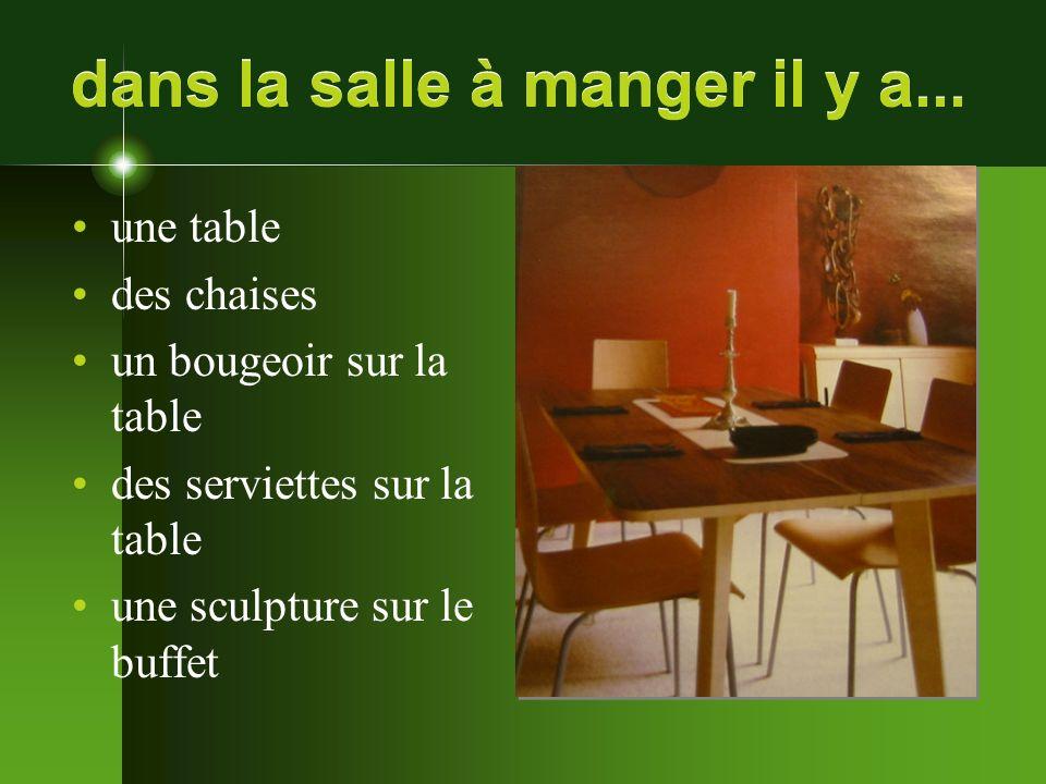 dans la salle à manger il y a... une table des chaises un bougeoir sur la table des serviettes sur la table une sculpture sur le buffet