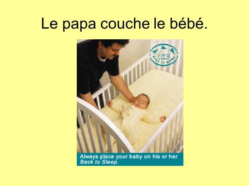 Le papa couche le bébé.