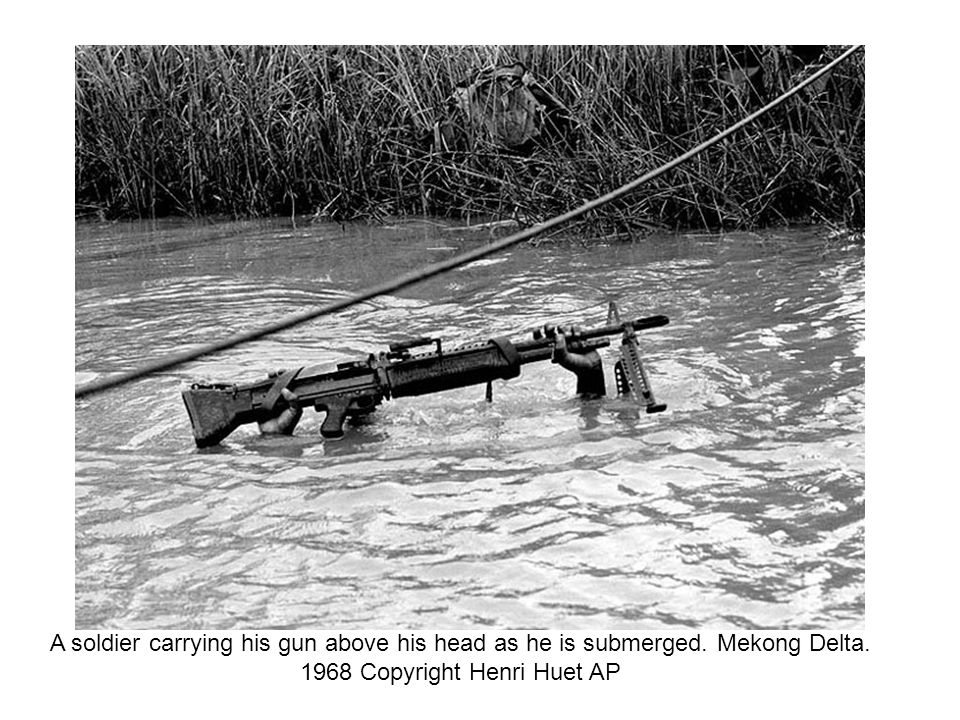 A soldier carrying his gun above his head as he is submerged. Mekong Delta. 1968 Copyright Henri Huet AP