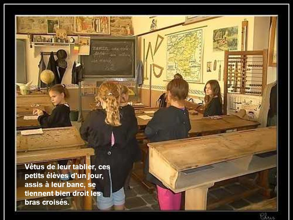 Vêtus de leur tablier, ces petits élèves d'un jour, assis à leur banc, se tiennent bien droit les bras croisés.