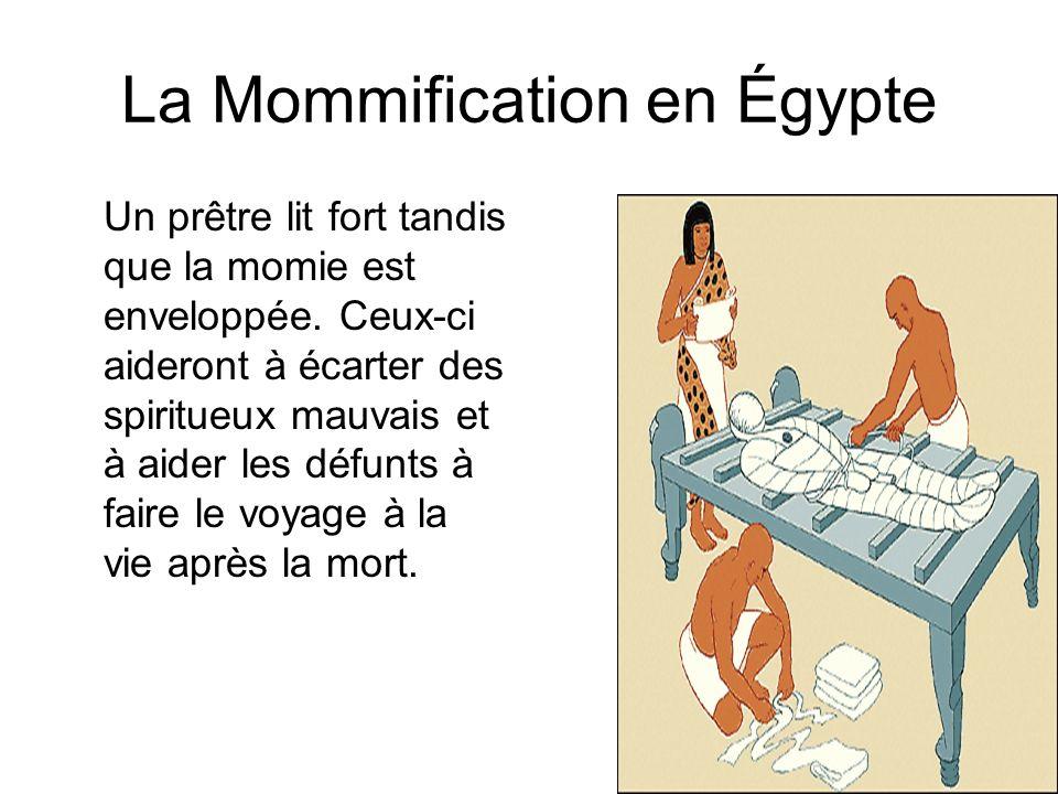 La Mommification en Égypte Un prêtre lit fort tandis que la momie est enveloppée. Ceux-ci aideront à écarter des spiritueux mauvais et à aider les déf