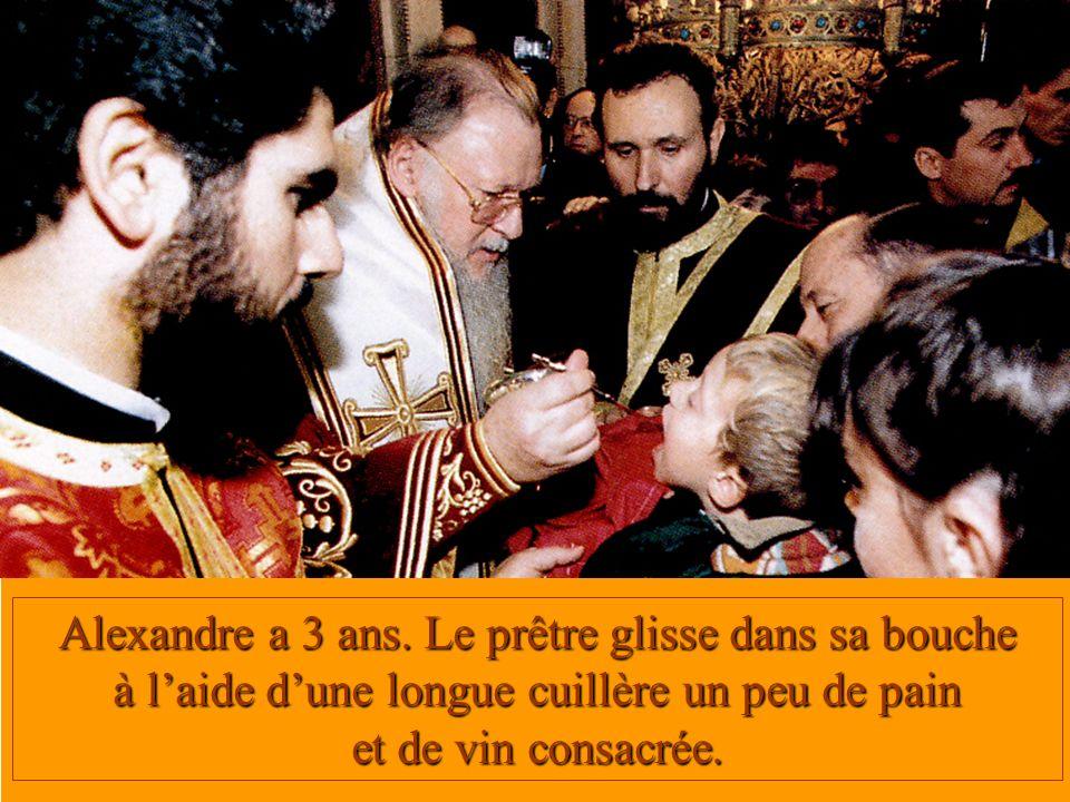 Alexandre a 3 ans. Le prêtre glisse dans sa bouche à laide dune longue cuillère un peu de pain et de vin consacrée.