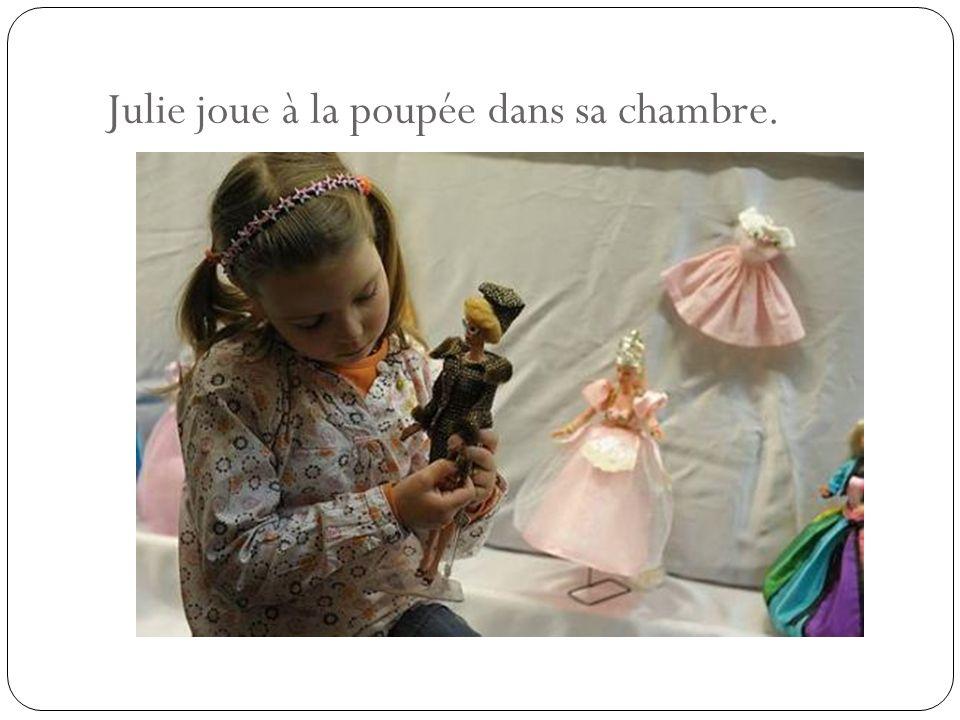 Julie joue à la poupée dans sa chambre.