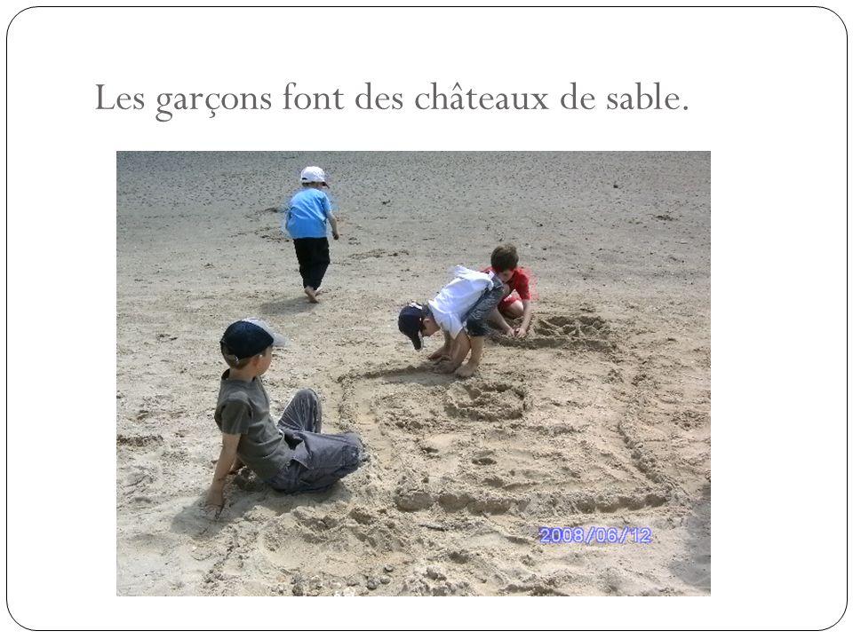 Les garçons font des châteaux de sable.