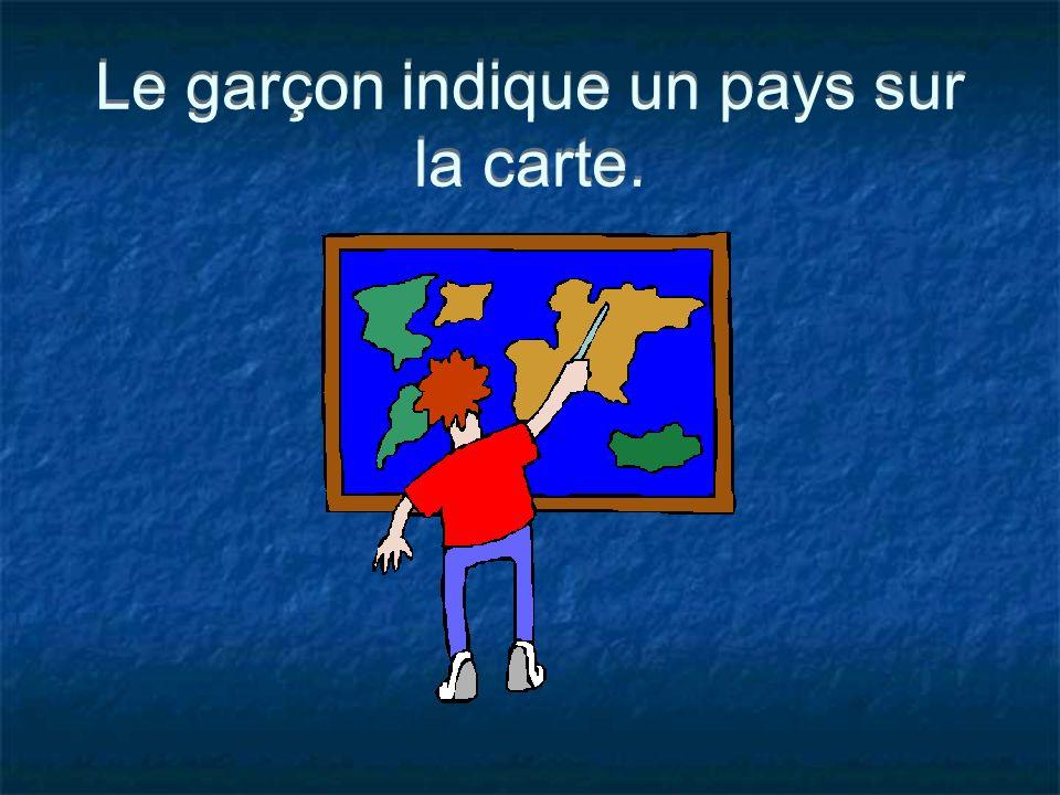 Le garçon indique un pays sur la carte.