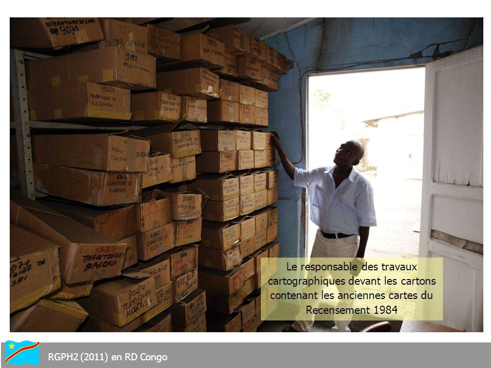 Le responsable des travaux cartographiques devant les cartons contenant les anciennes cartes du Recensement 1984 RGPH2 (2011) en RD Congo