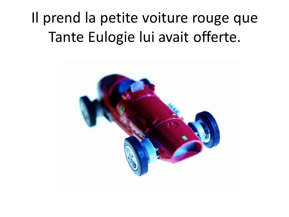 Il prend la petite voiture rouge que Tante Eulogie lui avait offerte.