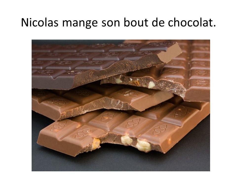 Nicolas mange son bout de chocolat.