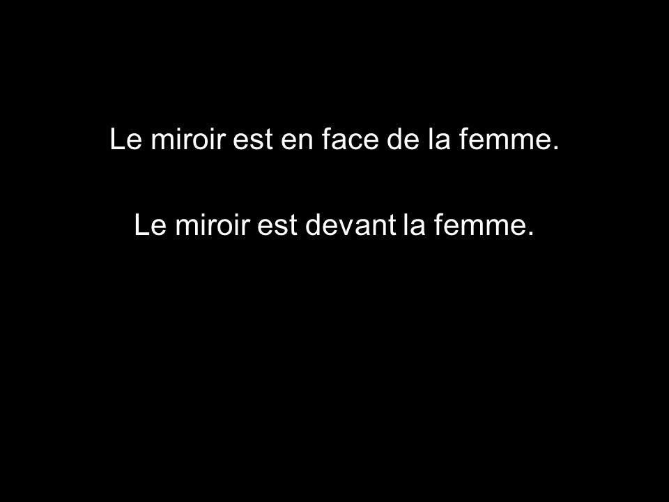 Le miroir est en face de la femme. Le miroir est devant la femme.