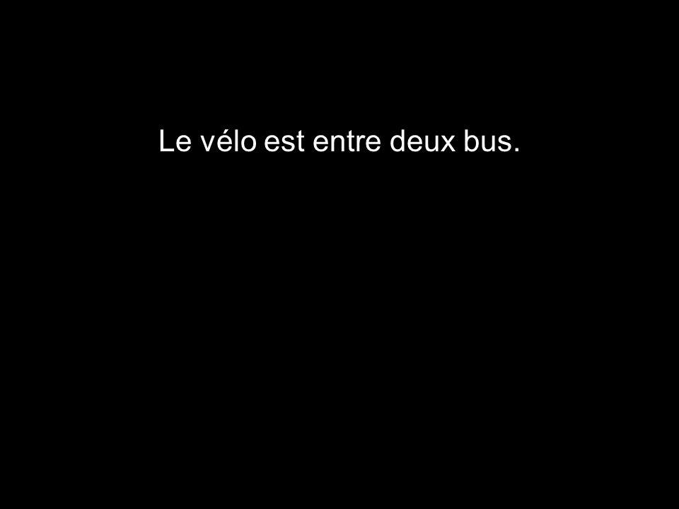 Le vélo est entre deux bus.