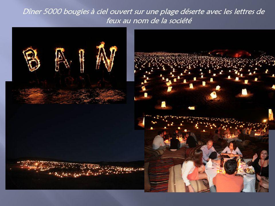 Dîner 5000 bougies à ciel ouvert sur une plage déserte avec les lettres de feux au nom de la société