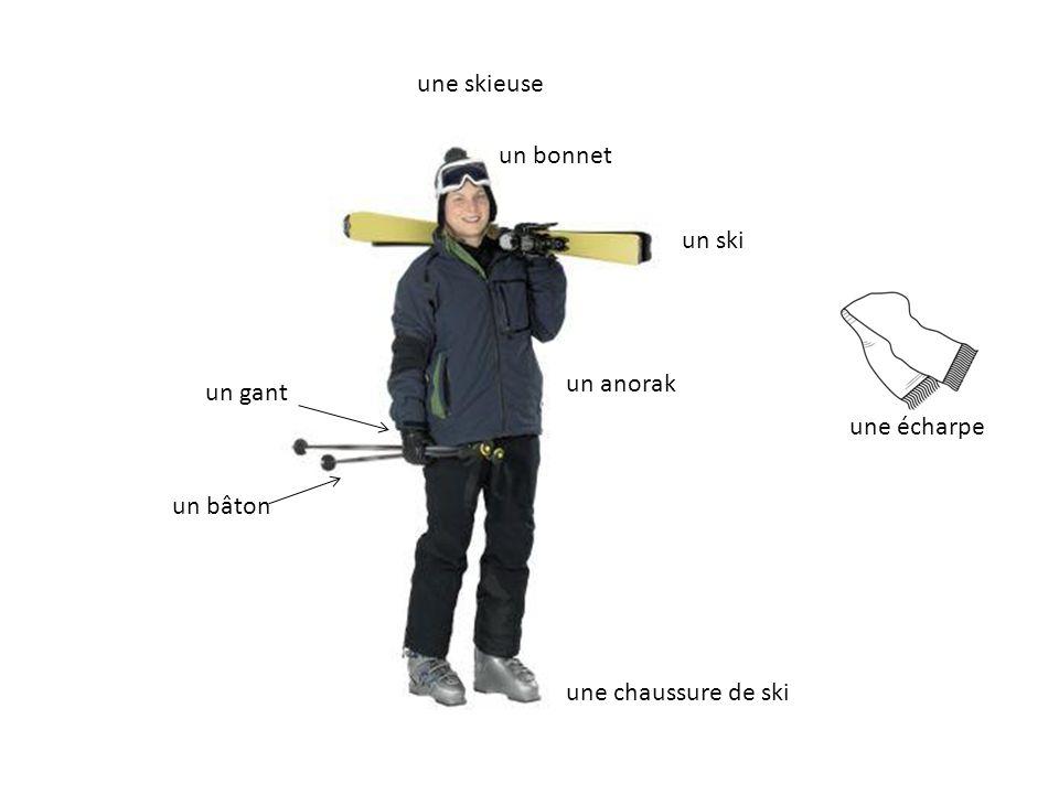 une skieuse un bonnet un anorak un bâton une chaussure de ski un ski un gant une écharpe
