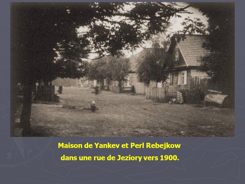 La boutique et maison de Yankev et Perl Rebejkow à Jeziory, vers 1900. Le panneau en russe indique qu'ils vendent : du blé, de la farine, du gruau et