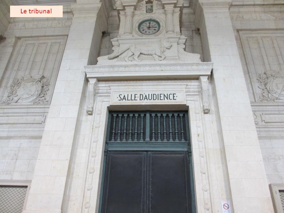 Deux statues à l'entrée du tribunal représentant les symboles de la Justice.