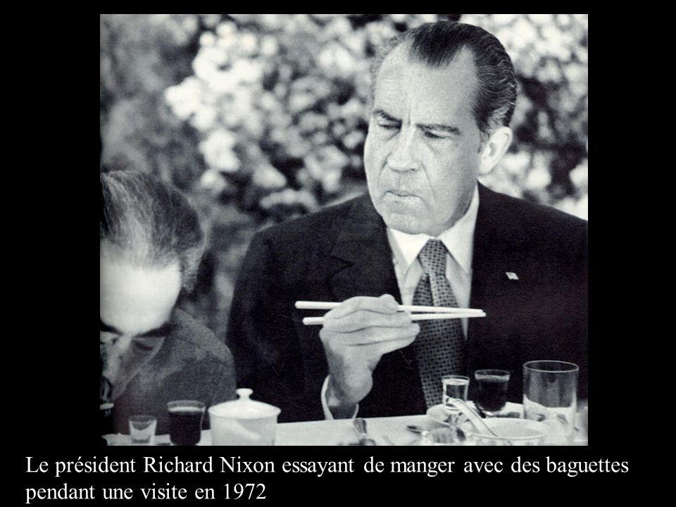 Le président Richard Nixon essayant de manger avec des baguettes pendant une visite en 1972