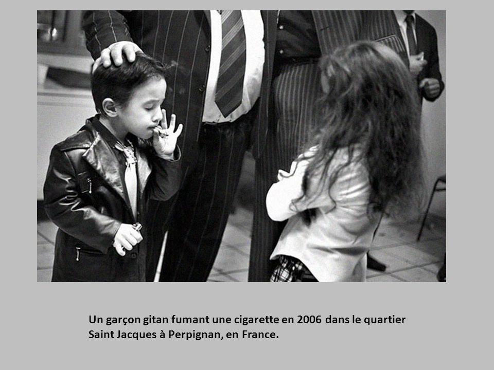 Une fille tenant la main de sa mère 6 ans après que cette dernière ait été déportée dans son pays natal. Elles sont séparées par la barrière qui symbo