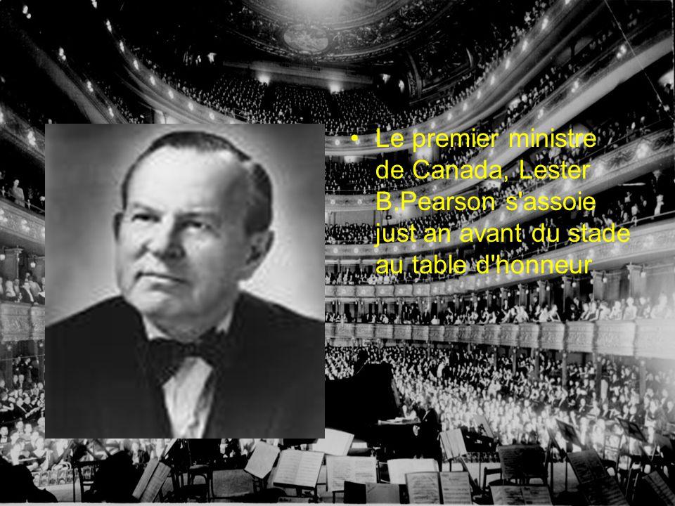 Le premier ministre de Canada, Lester B.Pearson s assoie just an avant du stade au table d honneur