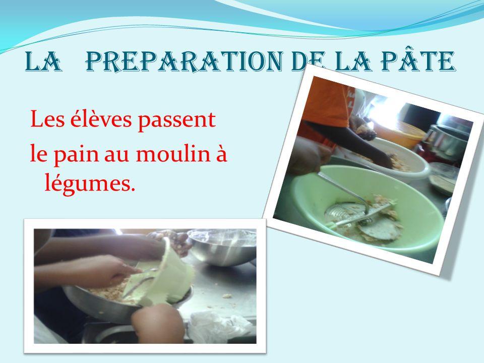 LA PREPARATION DE LA PÂTE Les élèves passent le pain au moulin à légumes.
