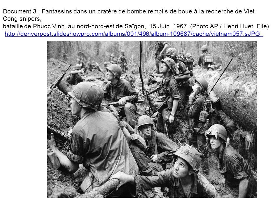 Document 3 : Fantassins dans un cratère de bombe remplis de boue à la recherche de Viet Cong snipers, bataille de Phuoc Vinh, au nord-nord-est de Saïg
