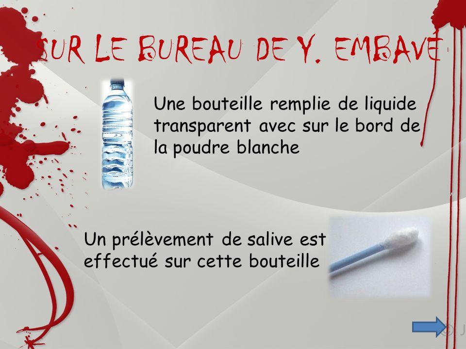 Une bouteille remplie de liquide transparent avec sur le bord de la poudre blanche Un prélèvement de salive est effectué sur cette bouteille SUR LE BU