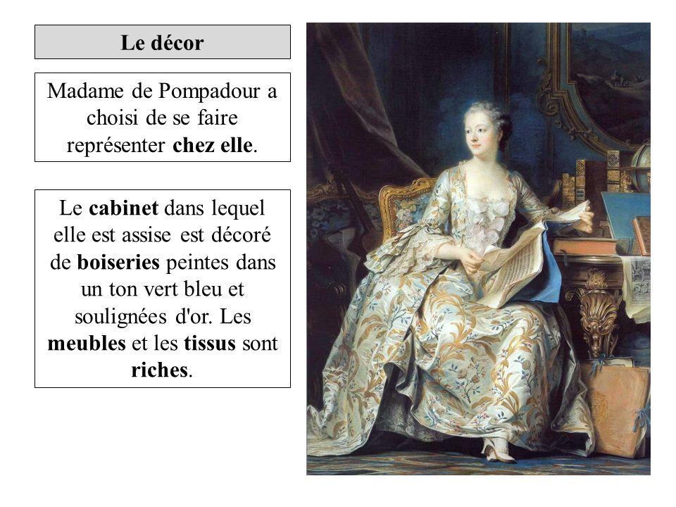 Le cabinet dans lequel elle est assise est décoré de boiseries peintes dans un ton vert bleu et soulignées d'or. Les meubles et les tissus sont riches