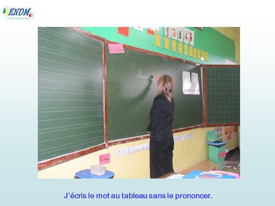 Jécris le mot au tableau sans le prononcer.