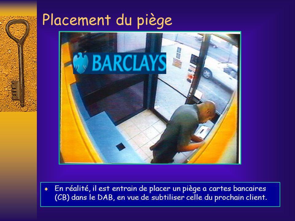 En réalité, il est entrain de placer un piège a cartes bancaires (CB) dans le DAB, en vue de subtiliser celle du prochain client. Placement du piège