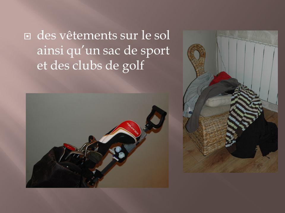 des vêtements sur le sol ainsi quun sac de sport et des clubs de golf