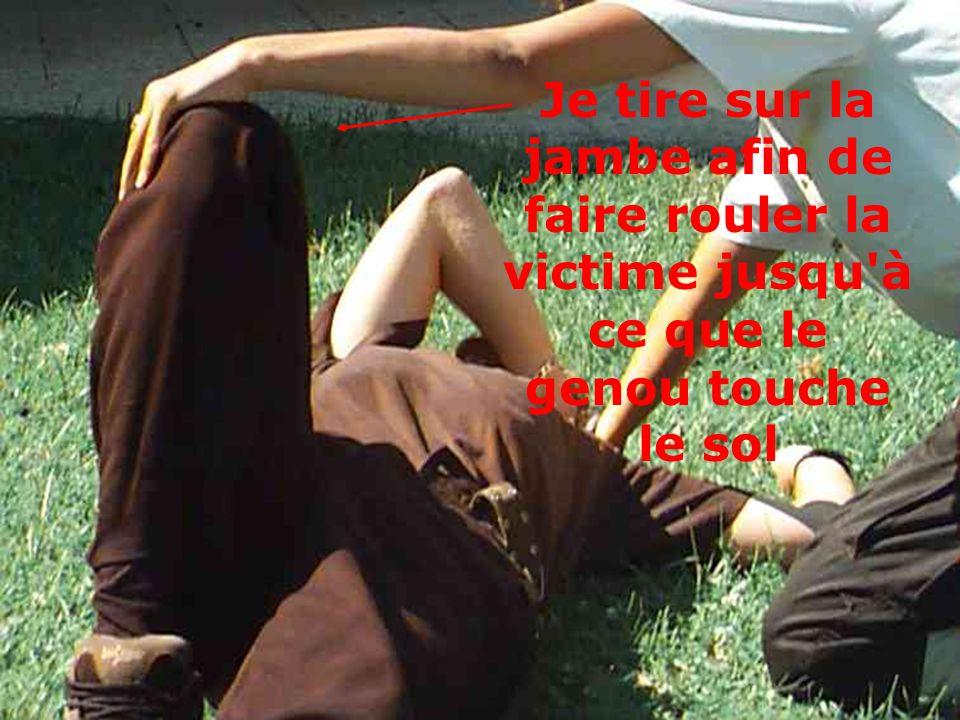 Je tire sur la jambe afin de faire rouler la victime jusqu'à ce que le genou touche le sol