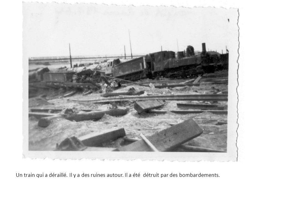 Un train qui a déraillé. Il y a des ruines autour. Il a été détruit par des bombardements.