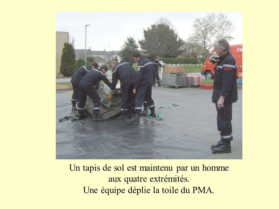 Un tapis de sol est maintenu par un homme aux quatre extrémités. Une équipe déplie la toile du PMA.