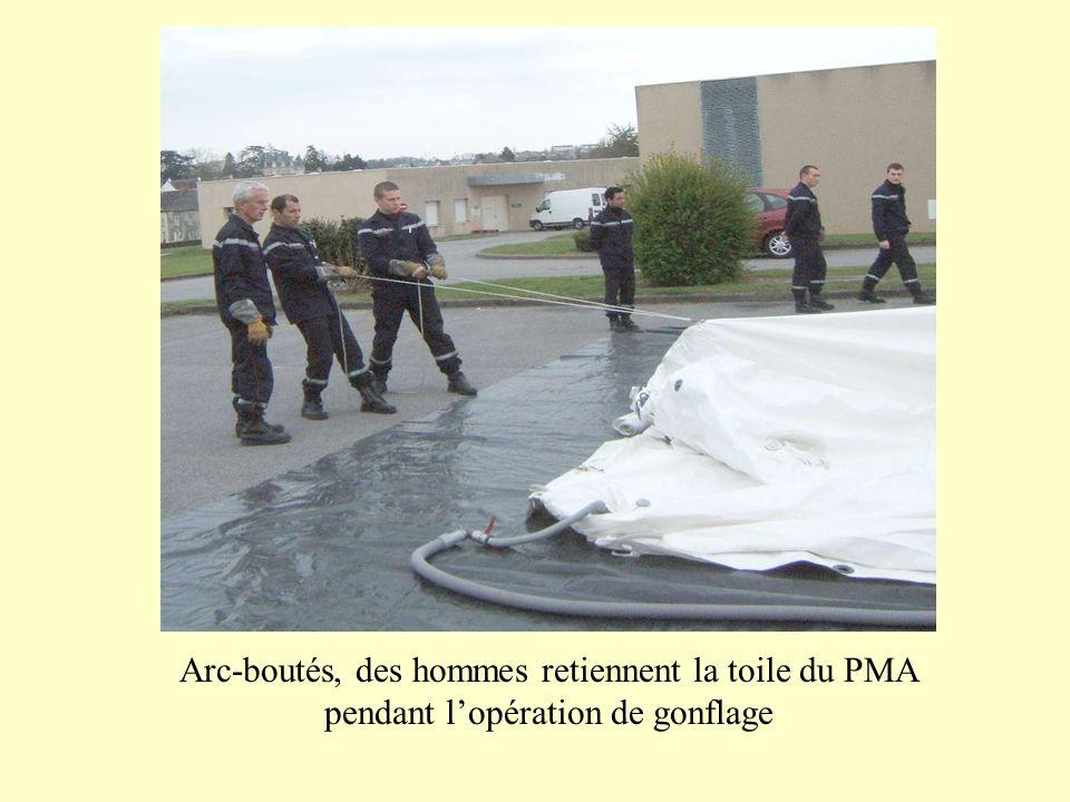Arc-boutés, des hommes retiennent la toile du PMA pendant lopération de gonflage