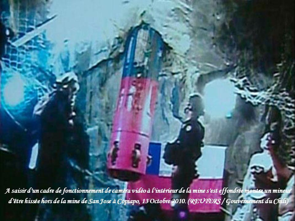 Travailleurs des mines et des représentants du gouvernement se penchant sur le trou de la capsule de sauvetage est abaissée Octobre 12, 2010 à la mine
