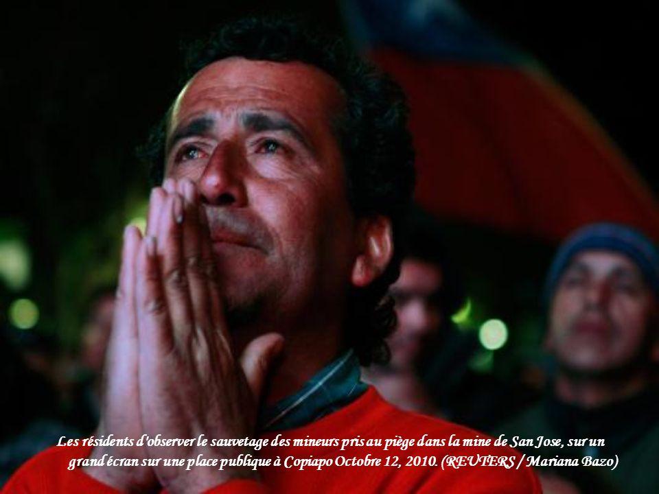 Les familles des mineurs et des journalistes montre le sauvetage de Florencio Avalos comme le premier des 33 mineurs pris au piège d'être hissé à la m