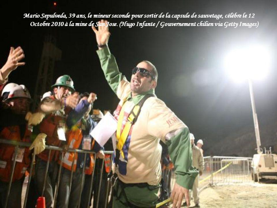Les gens célèbrent comme ils regardent à la télévision le premier mineur d'être secourus, Florencio Avalos, émergents en toute sécurité à la surface à