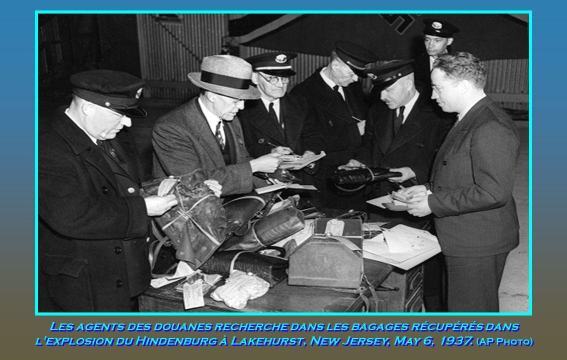 Des membres du Conseil inspecteurs de l'US Navy enquêtent près de l'épave du zeppelin allemand sur le terrain dans le New Jersey, le 8 mai 1937. (AP P