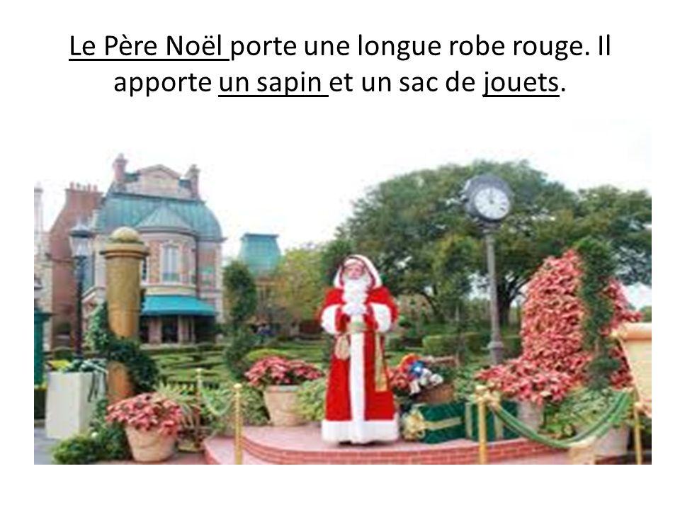 Le Père Noël porte une longue robe rouge. Il apporte un sapin et un sac de jouets.