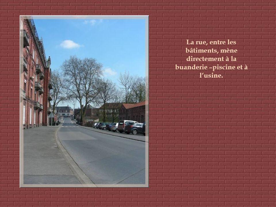 La rue, entre les bâtiments, mène directement à la buanderie –piscine et à lusine.