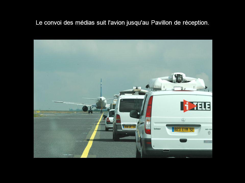 Le convoi des médias suit l'avion jusqu'au Pavillon de réception.